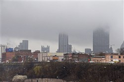In this April 19, 2018 file photo, a low layer of clouds cover part of the Downtown Pittsburgh skyline.