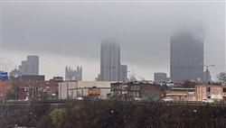 A low layer of clouds cover part of the skyline while the weather went back and forth from rain to snow in this view from the Birmingham Bridge looking toward the Bluff in this April 19, 2018, file photo.