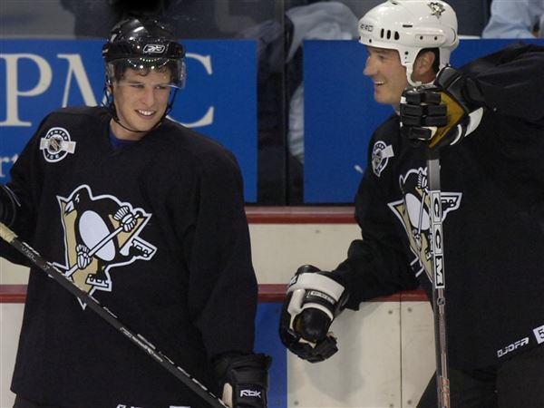 In this September 2015 file photo, Sidney Crosby, left, and Mario Lemieux take a break during a practice session at the old Mellon Arena in Downtown Pittsburgh.