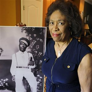 In this Wednesday, April 18, 2018 photo, Josephine Bolling McCall poses with a photo of her father, lynching victim Elmore Bolling, at her home in Montgomery, Ala.