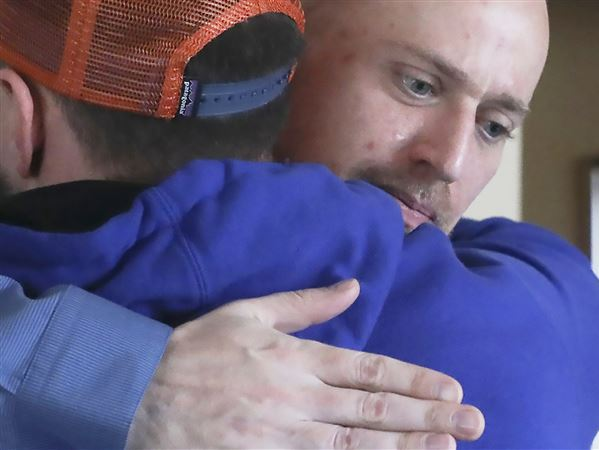 Andrew Caryl, 33, a graduate student in the mental health and rehabilitation counseling program at West Virginia University, right, hugs Blair Lawson, left, after a weekly group meditation and book study session Wednesday at Serenity Place, the university's collegiate recovery program, in Morgantown. Caryl has been clean for three years, after being addicted to alcohol, opioids and other drugs, but he finds that his place and leadership at Serenity Place continues to help him through his recovery.