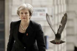 A pigeon takes off as Britain's Prime Minister Theresa May arrives at St Martin-in-the-Fields church in London on April 23, 2018.