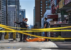 Police officers stand by a covered body in Toronto after a van mounted a sidewalk and crashed into a crowd of pedestrians on Monday.
