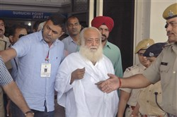 In this Sept. 1, 2013, file photo, controversial spiritual guru Asaram Bapu, center, is brought for interrogation by police at Jodhpur airport in Jodhpur, India.