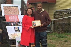 "Constanza Romero Wilson presents Mark Clayton Southers with a plaque to honor his Pittsburgh Playwrights Theatre Company's completion of August Wilson's Century Cycle of plays. PPTC is in its second turn around the cycle, including ""King Hedley II,"" which was to open April 27 -- August Wilson's birthday -- but was canceled due to expected thunderstorms."