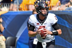 Oklahoma State quarterback Mason Rudolph breaks a tackle by Pitt s Amir  Watts to throw for a c39528477