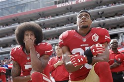 FILE - In this Oct. 2, 2016, file photo, San Francisco 49ers quarterback Colin Kaepernick, left, and safety Eric Reid kneel during the national anthem before an NFL football game against the Dallas Cowboys in Santa Clara, Calif.