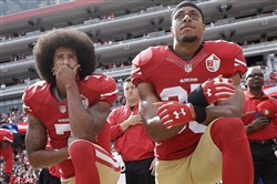 In October 2016, San Francisco 49ers quarterback Colin Kaepernick, left, and safety Eric Reid kneel during the national anthem.