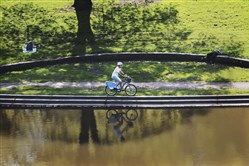A cyclist rides along the bank of the Panther Hollow Lake area on Wednesday, May 9, 2018 in Schenley Park. Pittsburgh officials have a $41 million flood mitigation plan for Panther Hollow and neighboring Junction Hollow to protect residents in the lower Greenfield area. Additionally, a key component of the plan includes dredging 5500 cubic yards from Panther Hollow lake.