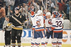 As Penguins star Mario Lemieux skates away, the New York Islanders celebrate a third-period goal by Steve Thomas in Game 6 of the 1993 NHL playoffs.