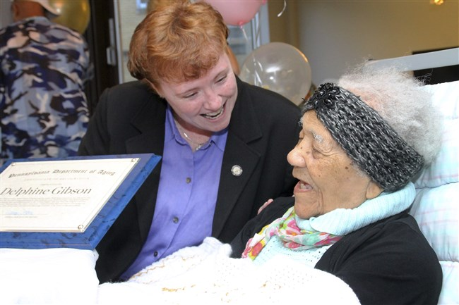 In this Aug. 16, 2017 file photo, state Department of Aging Secretary Teresa Osborne, left gives Delphine Gibson a commemorative plaque during her 114th birthday party while in her bed at AristaCare at Huntingdon Park, in Huntingdon, Pa.