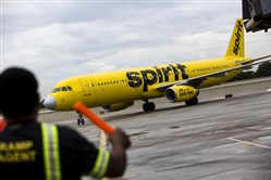 An aircraft marshal guides a Spirit Airlines plane on the tarmac at Fort Lauderdale International Airport in Fort Lauderdale, Florida, on June 2, 2017.