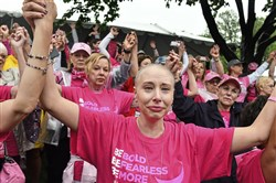 Rebecca Flores center, of Whitehall, holds hands with fellow participants on Sunday following the Survivors & Thrivers Parade during the Susan G. Komen Pittsburgh Race for the Cure in Oakland.