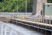 A worker walks past aeration basins on Monday, May 14, 2018, at the Allegheny County Sanitary Authority plant under the McKees Rocks Bridge.