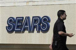 In this March 28, 2018, file photo, a man walks in front of a Sears sign in San Bruno, Calif. In a move announced Monday, May 14, Sears Holdings Corp. says a special committee of its board is starting a formal process to explore the sale of its Kenmore brand and related assets. (AP Photo/Jeff Chiu, File)