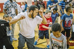 Allen Haley, center, of Sheraden, takes part in the dads vs. sons dance competition during Pittsburgh Langley K-8's Take a Father to School Day on Friday in Sheraden. Pittsburgh Public Schools invites fathers, grandfathers, uncles, and other positive male role models to accompany students to school for a day.