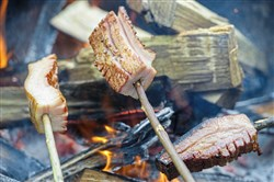 Guests roast bacon over an open fire at the 3rd annual Hungarian bacon roast at Huszar, a Hungarian bar and restaurant, on Saturday May 19, 2018, on the North Side.