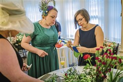 Rose Kocher, the lead designer at greenSinner Floral Event Design, helps Samantha Ellwood create a fascinator during the Royal Wedding Watch Party at the Mansions on Fifth  on Saturday, May 19, 2018 in Shadyside.