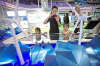 Visitors look at models of power-generating windmills at a booth for the China Energy Investment Corp. at the 21st China Beijing International High-tech Expo in Beijing, China on Friday. The annual expo is a showcase of China's state-of-the-art technologies and cutting-edge ideas.