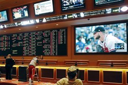 In this Monday, May 14, 2018 photo, people make bets in the sports book area of the South Point Hotel and Casino in Las Vegas.