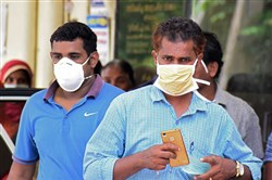 Indian residents wear face masks outside the Medical College hospital in Kozhikode on May 21, 2018.