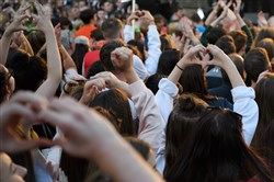 "People make the heart symbol with their hands during the ""Manchester Together - With One Voice"" tribute concert at Albert Square in Manchester, England, on May 22, 2018, the first anniversary of the arena-bombing terrorist attack in central Manchester."