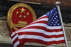 In this Nov. 9, 2017, file photo, an American flag is flown next to the Chinese national emblem during a welcome ceremony for visiting President Donald Trump outside the Great Hall of the People in Beijing.