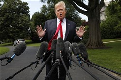 President Donald Trump's hair is ruffled by a breeze as he speaks to the media on the South Lawn of the White House in Washington on May 23, 2018, en route to a day trip to New York.