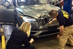 In this March 20, 2018, file photo NTSB investigators examine a driverless Uber SUV that fatally struck a woman in Tempe, Ariz.