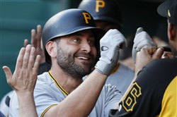 Pittsburgh Pirates' Francisco Cervelli celebrates in the dugout after hitting a two-run home run off Cincinnati Reds starting pitcher Homer Bailey during the first inning of a baseball game Wednesday, May 23, 2018, in Cincinnati.