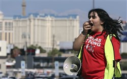 Volunteer Jenifer Murias yells into a megaphone as Culinary Union members file into a university arena to vote on whether to authorize a strike Tuesday in Las Vegas.
