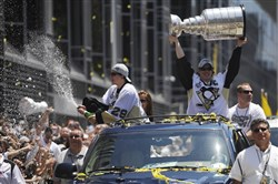 Sidney Crosby hoists the Stanley Cup and Marc-Andre Fleury sprays champagne into the air during the Penguins victory parade Downtown yesterday.