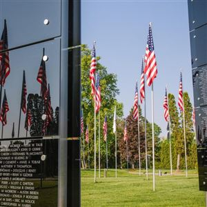 The Avenue of 444 Flags at Hillcrest Memorial Park cemetery reflects in the War on Terror Memorial on Thursday, May 24, 2018, in Hermitage. The flags were raised during the Iran hostage crisis and mark the 444 days of captivity. The War on Terror Memorial lists the names of more than 7,000 servicemen and women who have died in the war on terror.