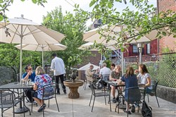 Lee Robinson plays his saxophone while restaurant-goers enjoy their meals on the patio of Piazza Talarico and Papa Joe's Wine Cellar in Lawrenceville.