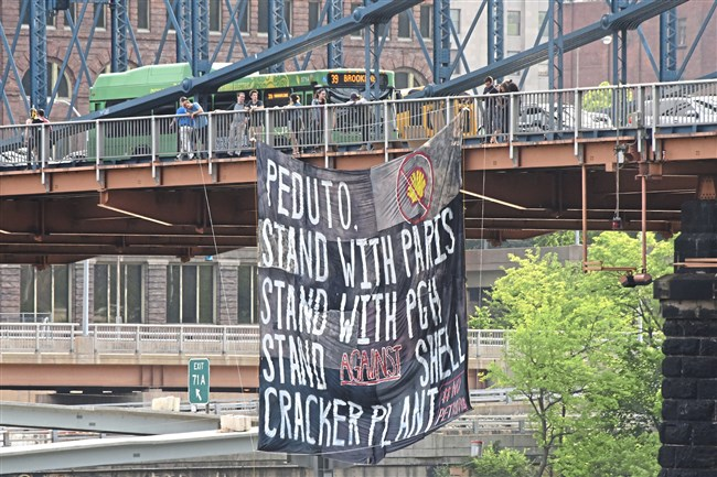 University of Pittsburgh students and alumni hang a banner on the Smithfield Street Bridge on Friday, June 1. They feel that Mayor Bill Peduto should publically oppose the Shell cracker plant, located in Beaver County.