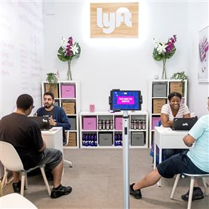 Community associates Norman Laborde, left, and Na-Tasha McClain-Hubbard help lyft drivers at the driver hub on Tuesday, June 12, 2018 at Blue Wave Auto Spa. Lyft is setting up a driver hub where independent contractors working on the ride-hailing service's network can stop in and use the restroom, troubleshoot with real people and get discounted auto services. (Antonella Crescimbeni/Post-Gazette)