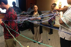 Annie Mickens of Petersburg, Va., center, plays the role of a child in a trauma-affected community during a training workshop held by FOCUS Pittsburgh at Duquesne Unversity. She is surrounded by people role-playing a variety of influences, and the yarn represents constraints caused by negative influences.