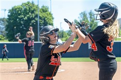 Upper Dauphin's Lea Lenker and Upper Dauphin's Eileen Nestor celebrate scoring their team's two runs against Mohawk in the PIAA Class 2A softball championship. Upper Dauphin beat Mohawk, 2-1.