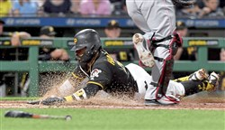 Pirates second baseman Josh Harrison scores against the Reds in the sixth inning Friday, June 15, 2018 at PNC Park.