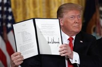 President Donald Trump holds up a space-policy executive order that he signed during a meeting of the National Space Council at the East Room of the White House on June 18, 2018, in Washington.
