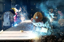 This file picture taken May 3, 2018, shows a worker cutting steel at a factory in Huaibei in China's eastern Anhui province.