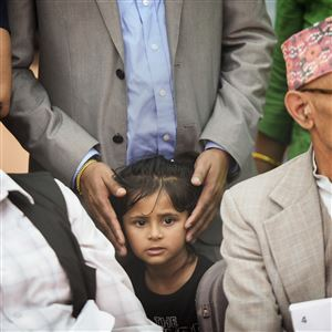 Nimisha Prasai, 3, stands with her father, Krishna, and waits during a ceremony in which her grandfather, Chhabi Prasai, left, became and American citizen during a World Refugee Day celebration at Market Square on Wednesday. At right is Hari Khatiwada, who also became a citizen. Both men are from Bhutan.