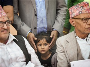Nimisha Prasai, 3, stands with father Krishna and waits during a ceremony in which her grandfather Chhabi Prasai (left) became and American citizen during a World Refugee Day celebration at Market Square on Wednesday, June 20, 2018. At right is Hari Khatiwada, who also became a citizen. Both men are from Bhutan.