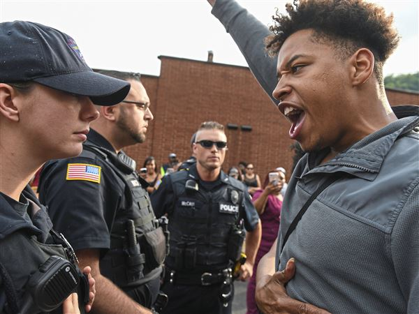 Christian Carter, 18, of East Liberty confronts a police officer during a rally in East Pittsburgh on Wednesday to protest the shooting death of Antwon Rose by an East Pittsburgh police officer during a traffic stop.