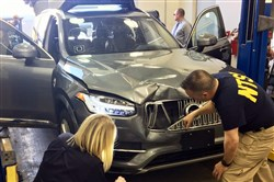 In this March 20, 2018 file photo provided by the National Transportation Safety Board, investigators examine a driverless Uber SUV that fatally struck a woman in Tempe, Ariz.