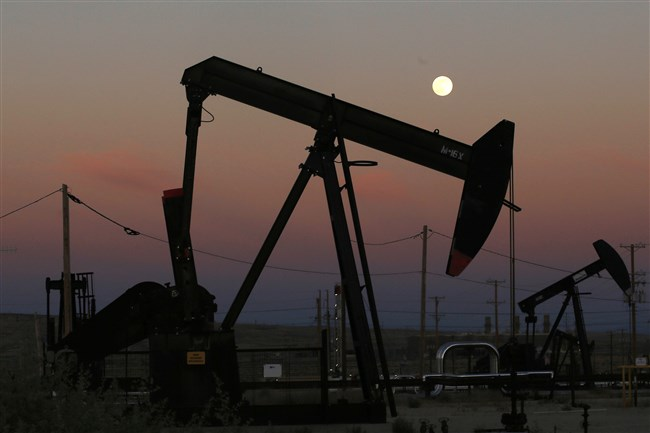 In this June 8, 2017, file photo, oil derricks are busy pumping as the moon rises near the La Paloma Generating Station in McKittrick, Calif.