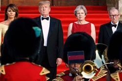 President Donald Trump, center left; Britain's Prime Minister Theresa May, center right; U.S. first lady Melania Trump, far left; and Philip May, the spouse of the prime minister, far right, stand on the steps in the Great Court to watch the bands of the Scots, Irish and Welsh Guards perform a ceremonial welcome as they arrive for a black-tie dinner with business leaders at Blenheim Palace, west of London, on July 12, 2018, on the first day of Mr. Trump's visit to the U.K.