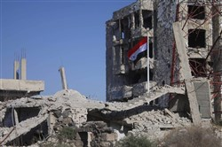 The Syrian national flag rises in the midst of damaged buildings in Daraa-al-Balad, an opposition-held part of the southern city of Daraa, on July 12, 2018.