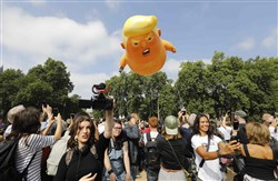 Protesters gather around a giant balloon depicting President Donald Trump as an orange baby during a demonstration against Trump's visit to the UK in Parliament Square in London on July 13, 2018.