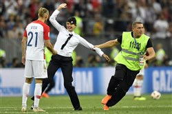 A steward pulls a woman off the pitch after she stormed onto the field and interrupted the final match between France and Croatia at the 2018 soccer World Cup in the Luzhniki Stadium in Moscow on July 15, 2018.